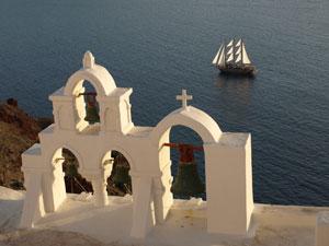 Klokkentorens met zeilboot in Oia op Santorini